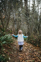 Back View of A Little Girl Boldly walking along a Forest Path in Fall