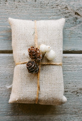 Christmas gift wrapped with linen and decorated with natural items.
