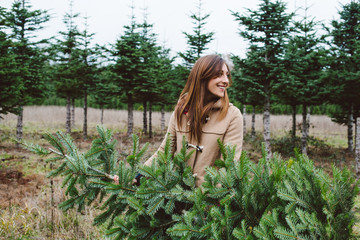 Beautiful young woman carry christmas tree in wooded field in the winter.