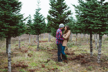 Attractive young couple walking through tree farm together in the winter.