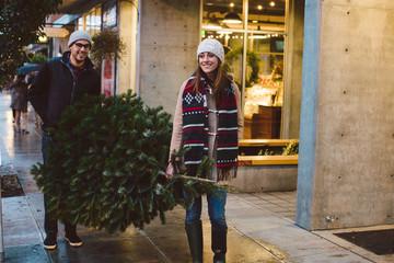 Couple walking down urban sidewalk with Christmas tree at dusk.