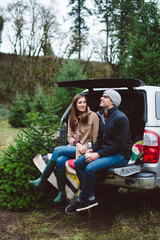 Couple sitting on the tailgate of a truck after cutting down their Christmas tree.