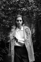 Attractive woman in trench coat looking at camera