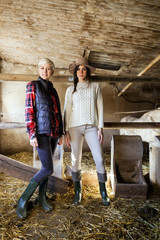 Portrait of women farmers standing on a stable.