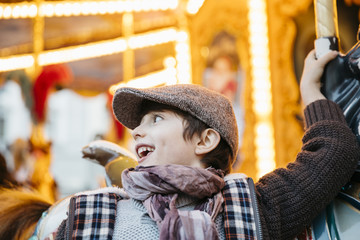 Boy's profile with a funny expression on a carousel