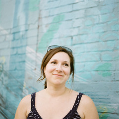 Smiling woman in front of aqua blue-green brick wall