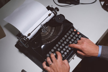 Man typing with a vintage typewriter