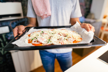 Closeup of a man showing a handmade Italian pizza at home.