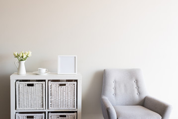 Living room with retro grey armchair, white roses, cup and saucer and blank square picture frame against neutral wall background