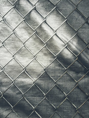 Close up of chain-link fence and silver tarp