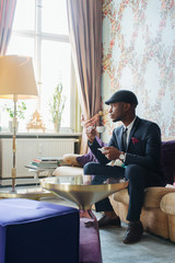 Handsome Young Black Man Sitting in Bright Living Room and Drinking Espresso