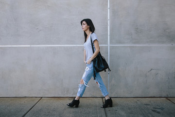 Trendy young woman walking with purse