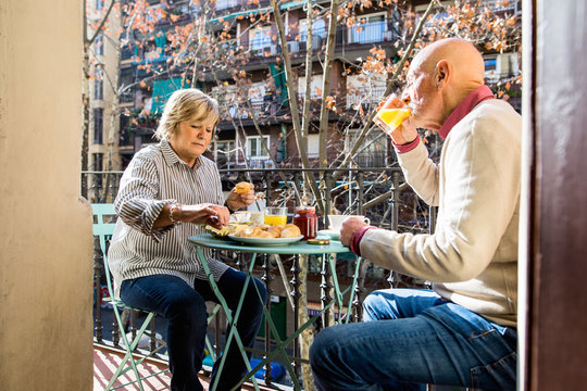 Elderly couple having a breakfast on balcony.