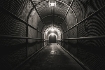A cold, dark, fenced walkway leads to darkness.