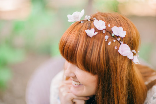 Portrait of a young beautiful redhead woman with long hair and green eyes with a paper flowers crown