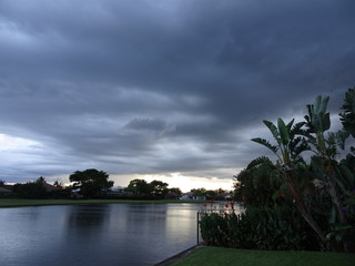 storm clouds and palm trees at sunset