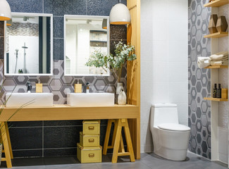 Bright and white bathroom with wooden vanity with a tiled counter. There are mirrors set above each sink. Horizontal shot.