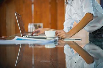 Image of young businessman with cup of coffee looking at laptop screen at workplace
