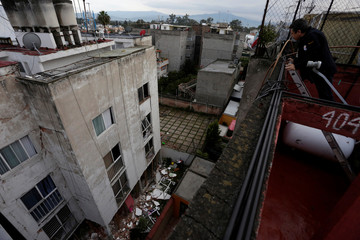 A man looks down from the roof of his home, at the rubble from a building damaged in an earthquake, in Mexico City