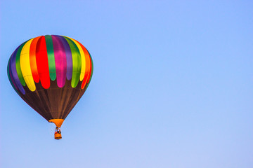 Multi Colored Hot Air Balloon Above Tree Line