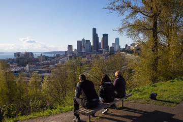 People relaxing on a bench with Downtown Seattle City Skyline in the Background. Picture taken in Dr. Jose Rizal Park, Washington, USA.
