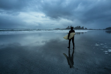 Surfer heading out in the ocean during a cloudy winter sunset. Picture taken in Chesterman Beach, Tofino, Vancouver Island, BC, Canada.
