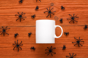 White coffee mug with decorative spiders on orange background.