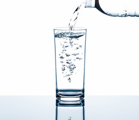 Drinking water pouring from bottle into glass with air bubbles with reflection on glass table isolated on white background