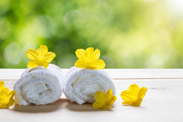 White towels with yellow flowers on wooden floor on blurred green bokeh background, spa concept