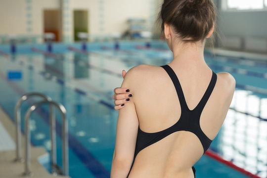 Close up sportsman with shoulder pain before swimming moment standing near poolside.