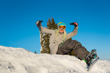 Smiling young female snowboarder sitting and having fun on top of the snowy slope outdoors on a beautiful sunny winter evening