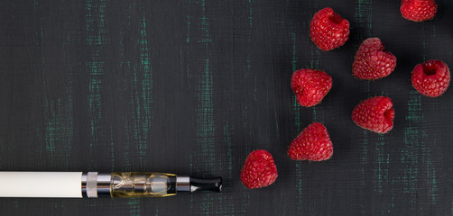 white electronic cigarette, lies on a black background, and out of it comes the smoke of a raspberry