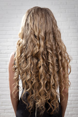 Hair wavy curls on the model of blonde rear view