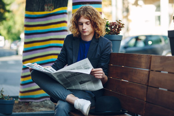 Red haired hipster man sitting on bench reading a newspaper