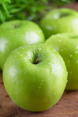 Ripe green apples with water dropletson wooden background