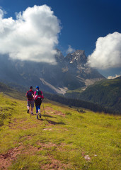 Couple of walking tourists in the mountains, Dolomites, Italy