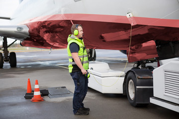 Ground Worker Standing By Airplane With Communication Cable On R
