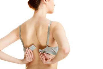 Attractive slim woman taking off grey bra