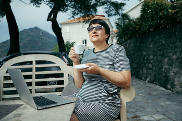 Senior woman drinks cofee and sitting on outdoors cafe with laptop
