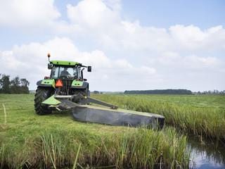farmer mows meadow in landscape near utrecht in the netherlands