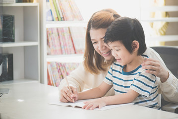 Asian mother helping her son doing homework