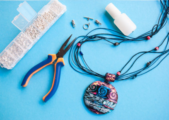 Assembly of beautiful boho pendant with pliers and tools. Working process of woman hobby. Making gift for friend.