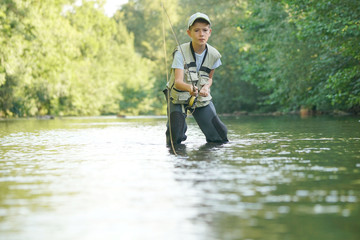 Young boy fly-fishing in river