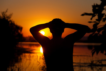 Silhouette of young man watching at river water