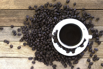 Coffee beans and black coffee cup on wood background. Top view with copy space for your text