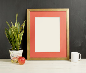 Frame mockup with plant pot, apple and mug