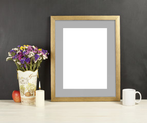 Brown frame mockup with field flowers in vase, apple, mug and candle