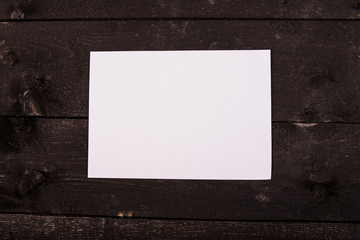 Obraz Drewniany stół z białą kartką na środku. Mock up. Mock up na menu, katalog. Starodawny stół. Drewniane tło. - fototapety do salonu