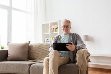 senior man with tablet pc sitting on sofa at home