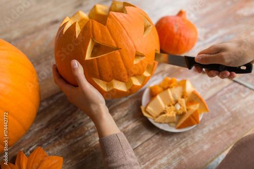 close up of woman carving halloween pumpkin